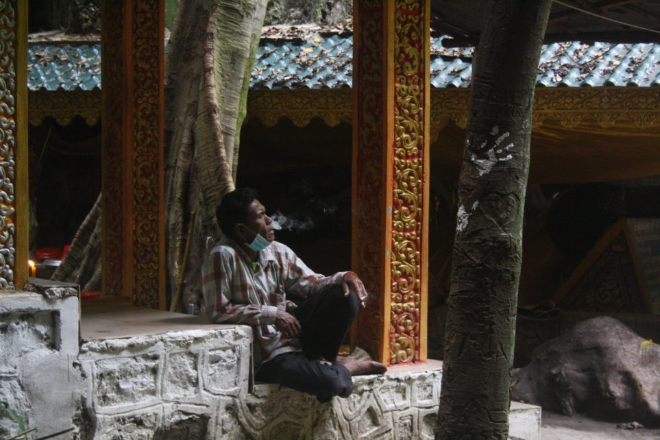 A man smokes a cigarette inside a cave at Kampong Trach in Kampot province on August 27, 2021. (Michael Dickison/VOD)