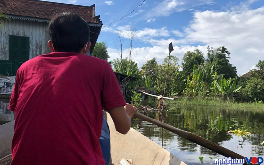 A young resident paddles home after his neighborhood in Chroy Changva has reportedly been flooded for two months. Officials earlier this year had reportedly filled a local canal. Photo taken October 10, 2021.